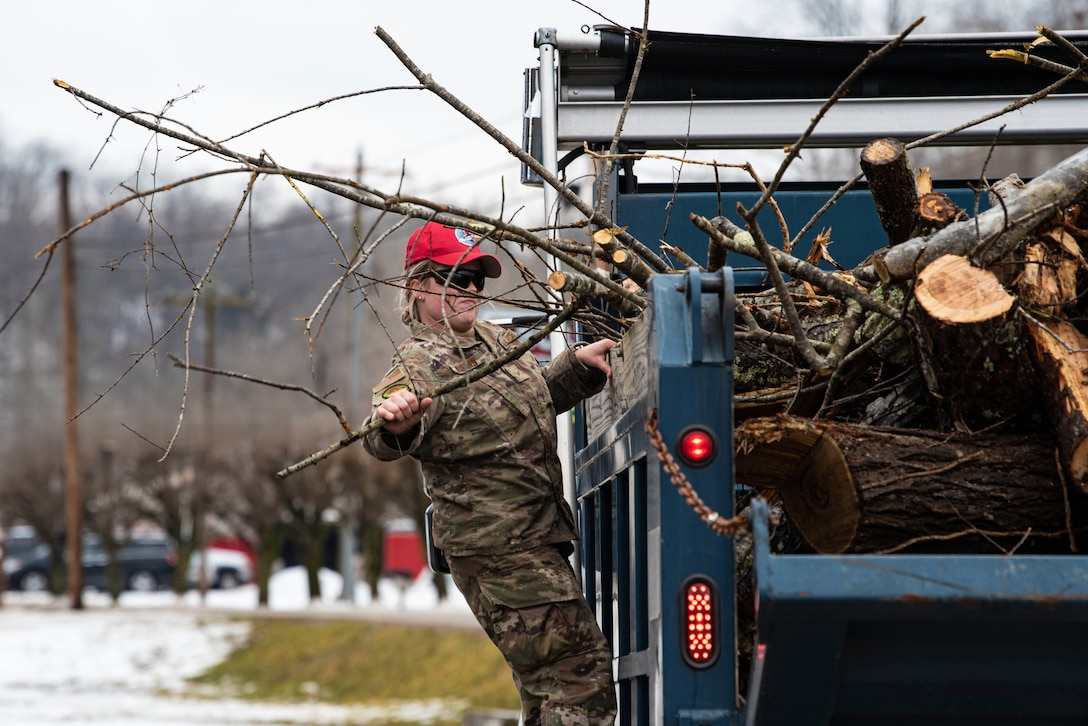 An airman adjusts tree debris in the back of a vehicle.