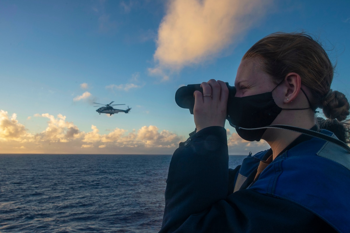 A sailor looks through binoculars from the deck of a ship with an aircraft on the horizon.