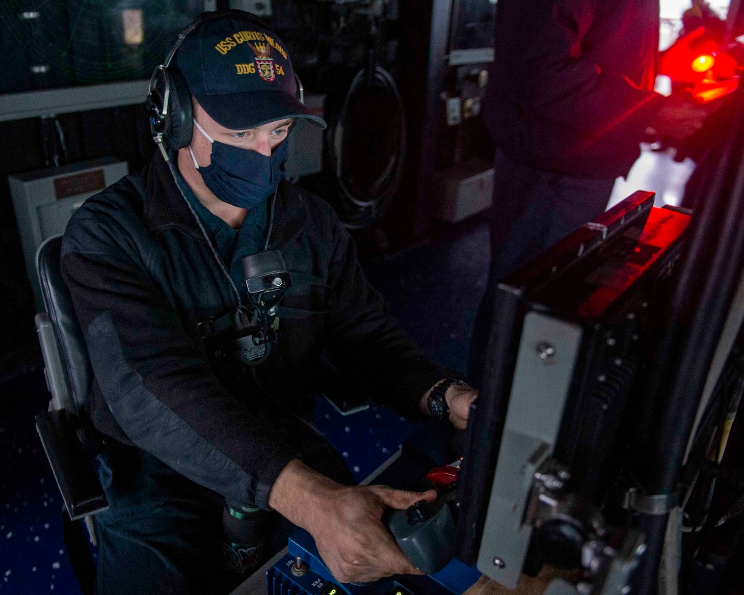 TAIWAN STRAIT (Feb. 23, 2020) -- Gunner's Mate 3rd Class Michael Griffith, from Chicago, monitors a live camera feed aboard the Arleigh Burke-class guided-missile destroyer USS Curtis Wilbur (DDG 54). Curtis Wilbur is assigned to Destroyer Squadron (DESRON) 15, the Navy's largest forward-deployed DESRON and the U.S. 7th Fleet's principal surface force.