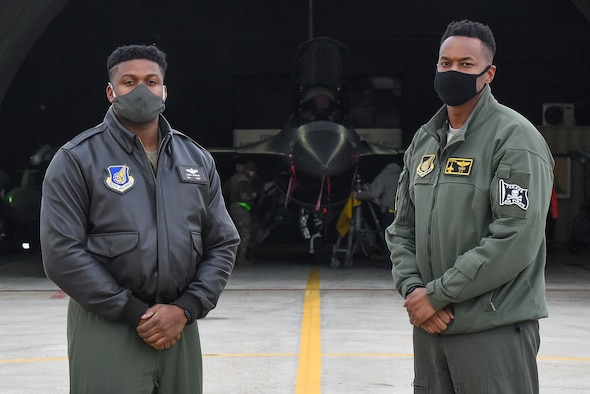 "Maj. Douglas ""Bane"" Jenkins, 8th Fighter Wing Advanced Programs Office program manager, and Maj. Chris ""Tuco"" Harrison, 8th Fighter Squadron assistant director of operations and chief of standards and evaluations, pose for a photo in front of an F-16 Fighting Falcon on the flightline at Kunsan Air Base, Republic of Korea, Feb. 17, 2021. Harrison and Jenkins attended Tuskegee University together and are now both assigned to the same unit at the Wolf Pack. (U.S. Air Force photo by Senior Airman Suzie Plotnikov)"