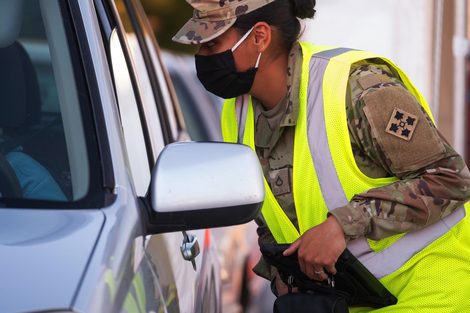 A female soldier wearing a face mask leans into the window of a vehicle.