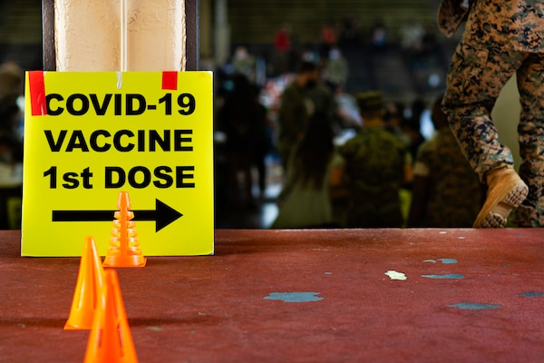 A sign on the floor points the way to COVID-19 vaccines as a service member walks down some stairs.