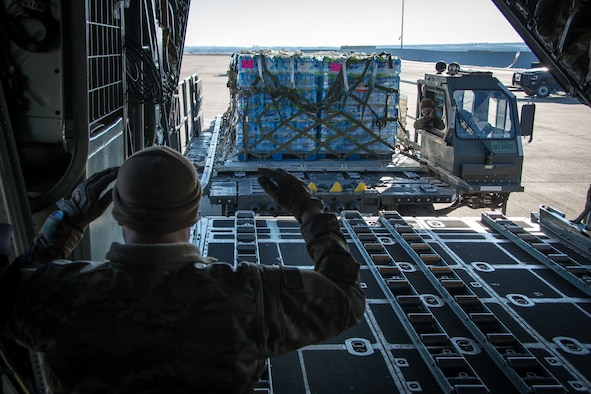 Texas Air National Guardsmen from the 181st Airlift Squadron load pallets of water on a C-130H Hercules Feb. 19, 2021, at Naval Air Station Joint Reserve Base Fort Worth, Texas. Several aircraft delivered bottled water to towns in South Texas after a devastating winter storm.