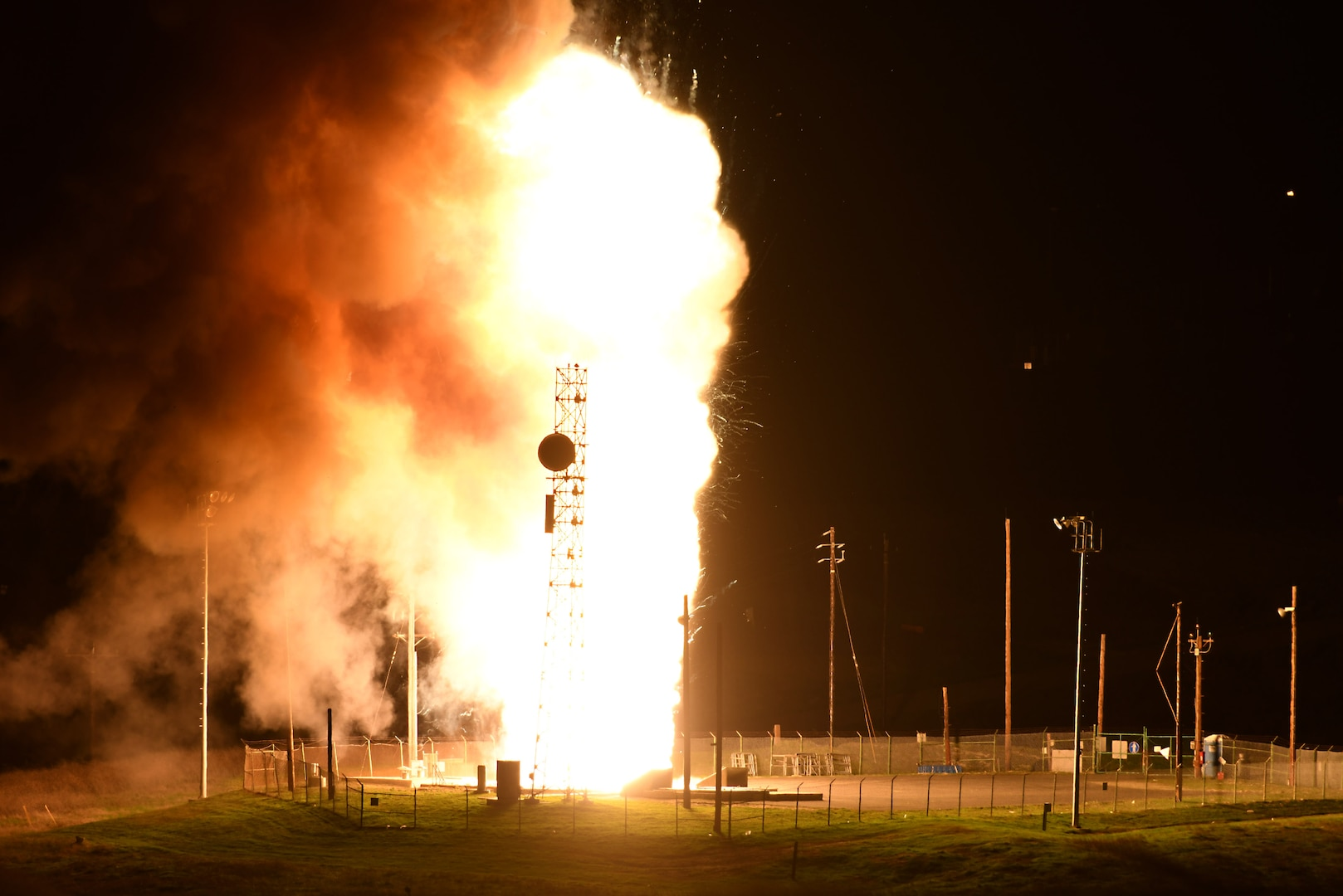 A fence surrounds a platform, as a column of flames billow against the night sky.