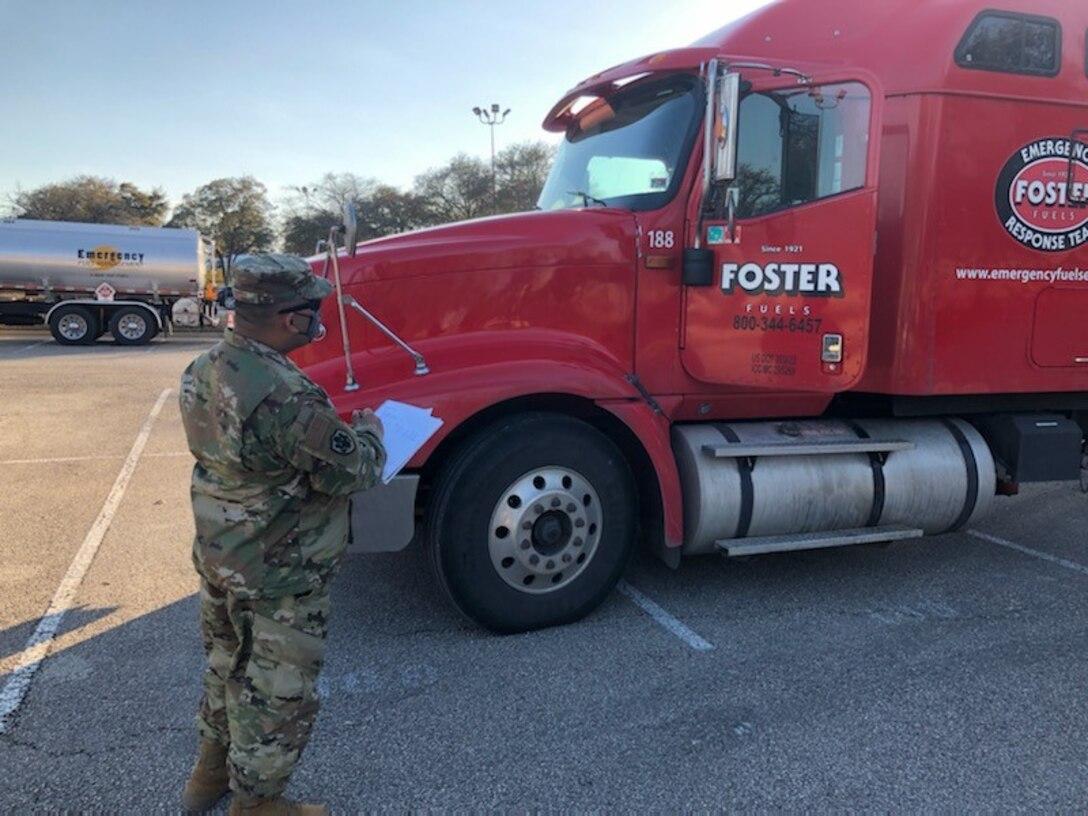A man in military uniform looks at a big fuel truck