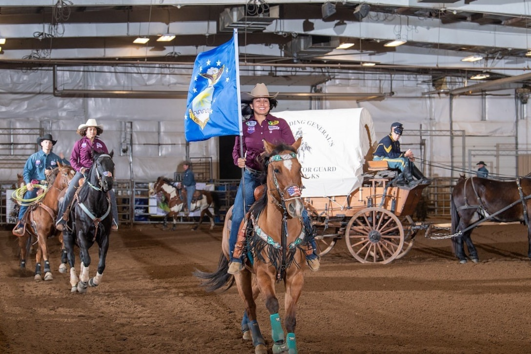 Master Sgt. Jenniffer Teets, 436th Comptroller Squadron, carries the Air Force flag while on horseback during a rodeo competition. (Courtesy photo)