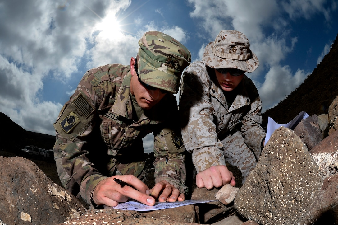 U.S. Army Cpl. Gregory McLellan and U.S. Marine Corps Cpl. Clinton Smith, Joint Corporals Leadership Development Course students, plot grid points during the land navigation portion of Camp Lemonnier's Joint Corporal's Leadership Development Course at Arta, Djibouti, March 3, 2016. During the evaluation Soldiers, Sailors, Airmen, and Marines had to find eight different points and navigate to those points in a timed event. (U.S. Air Force photo by Tech. Sgt. Dan DeCook)