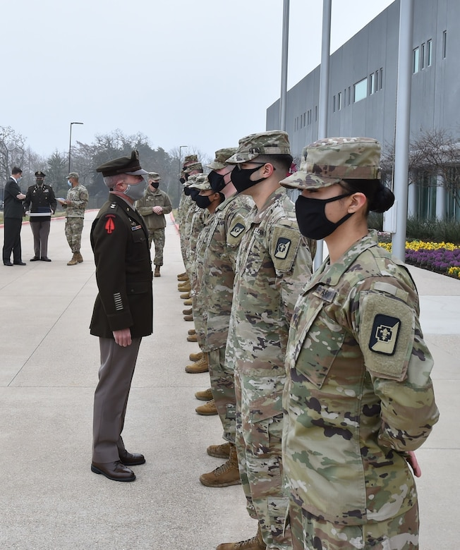 Soldiers wearing face masks stand at attention during an award ceremony.
