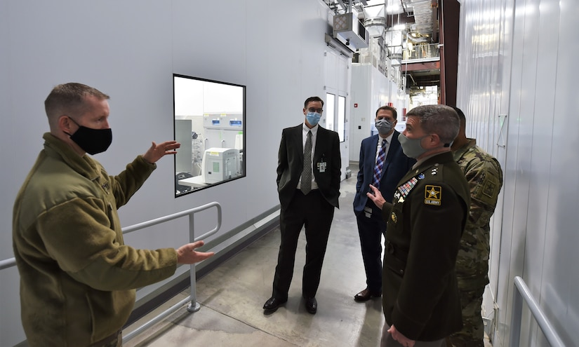 Army leaders wearing face masks discuss operations at a biotechnology facility.