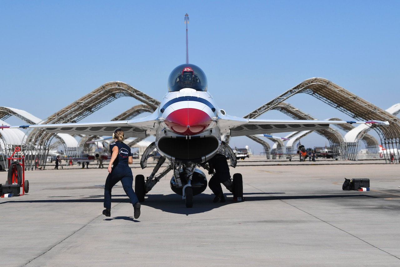 An airman runs toward the side of an aircraft.