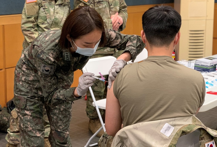 A South Korean Army nurse gives a soldier a shot in the arm.