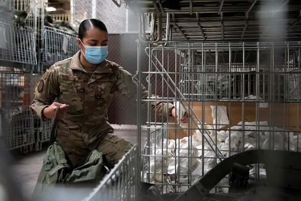 Senior Airman Genesis Robles-Rivas, a materiel manager in the 419th Logistics Readiness Squadron, selects glove inserts from a bin in preparation for training Feb. 7, 2021, at Hill Air Force Base, Utah.