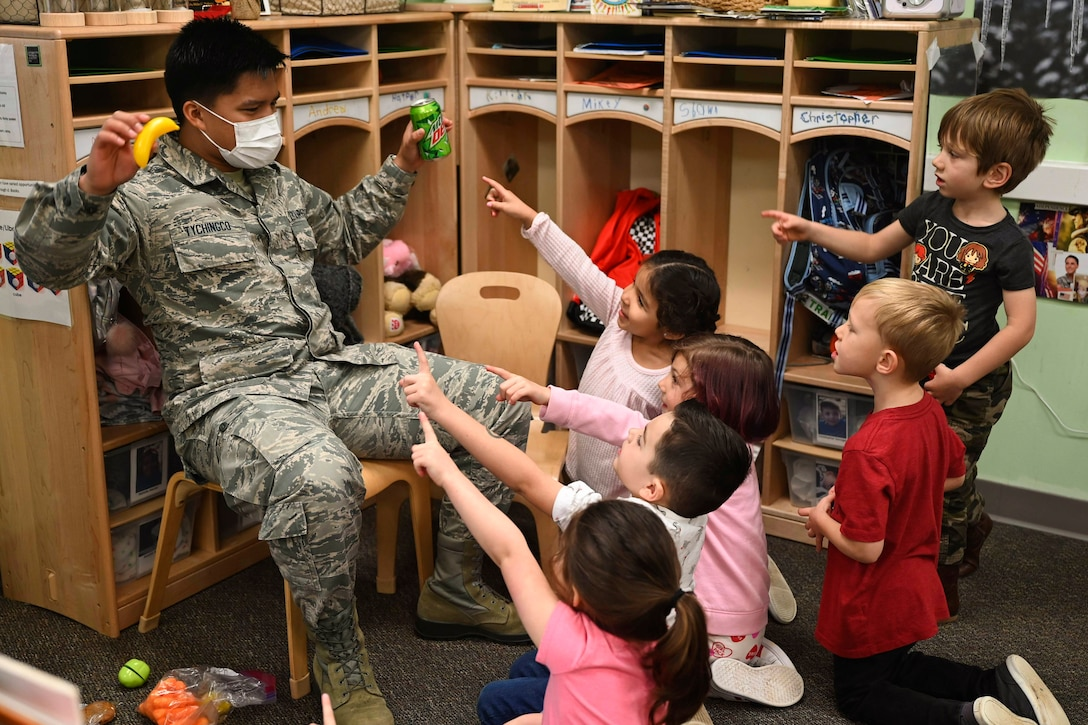 An airman holds up a soda and a banana while children point to them.