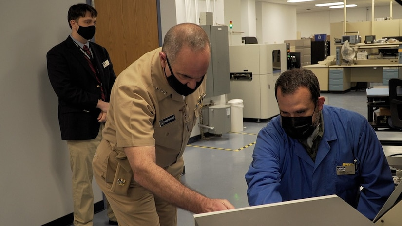 A Crane employee speaks with Strategic Command's senior leader Adm. Charles Richard in a lab.
