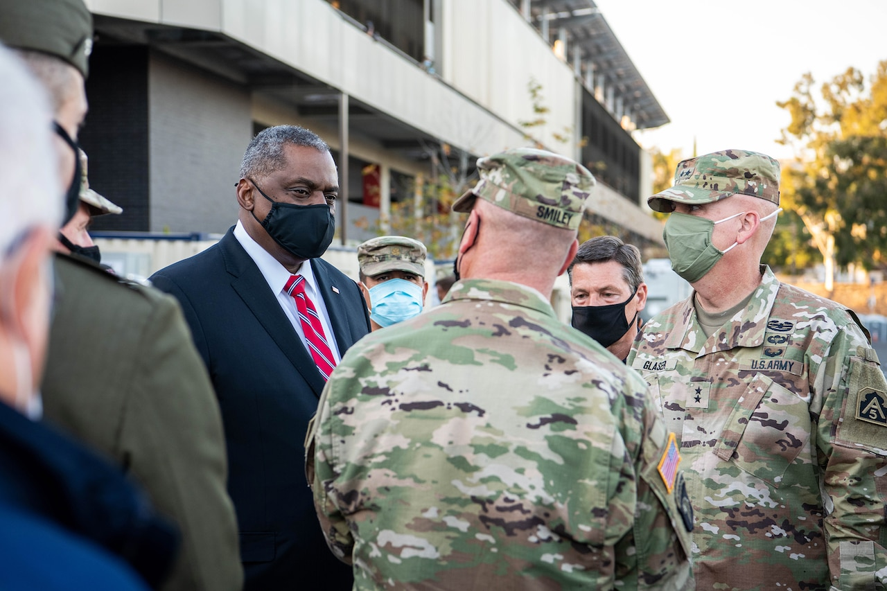Secretary of Defense Lloyd J. Austin III speaks to service members outside a building.