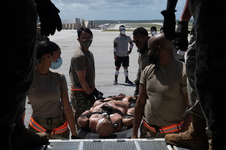 U.S. Air Force Airmen with the 36th Medical Group prepare to lift a patient into a bus for transport to a proper medical facility during an exercise at Andersen Air Force Base, Guam, Feb. 10, 2021.