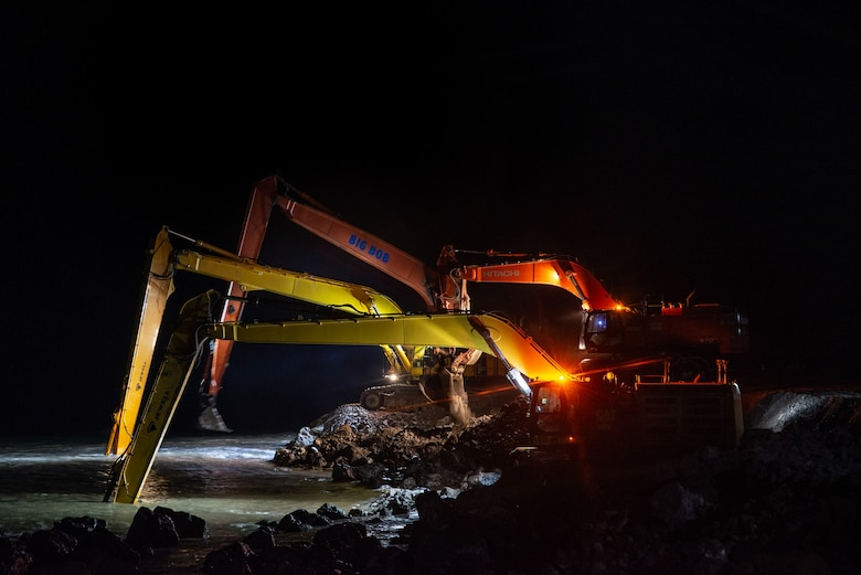 Long stick hydraulic excavators lay rocks in the late hours for the seawall repair at Cape Lisburne on Oct. 10, 2019.