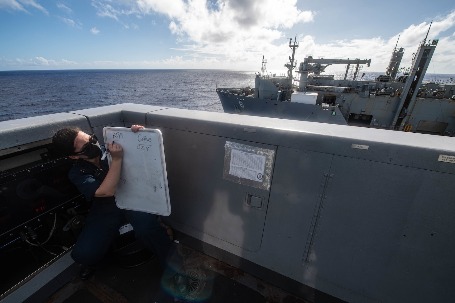 Lt. Christina Caracoza, from Los Angeles, notes course and speed changes aboard USS New Orleans (LPD 18) during a replenishment-at-sea with ship USNS Amelia Earhart (T-AKE 6).