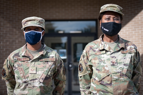 Two Airmen stand next to each other.