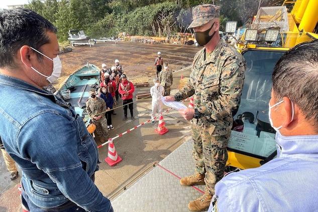 基地内の建設現場で働く西田典正さんと天久恵勝さんが2月25日、マシュー・トレーシー基地司令官から感謝状を贈られました。