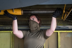 Royal Air Force member loads a boom support jack into a storage compartment