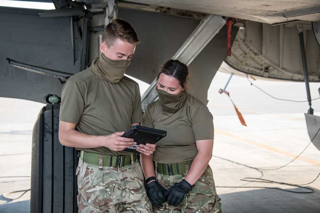 Royal Air Force members look at ipad while inspecting aircraft