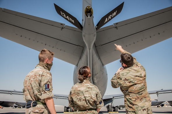 a pilot conducts a preflight inspection of an aircraft with royal air force members