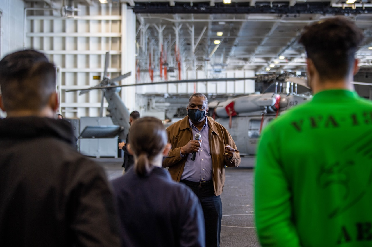 A man wearing a protective face masks speaks to a group of people on an aircraft carrier.