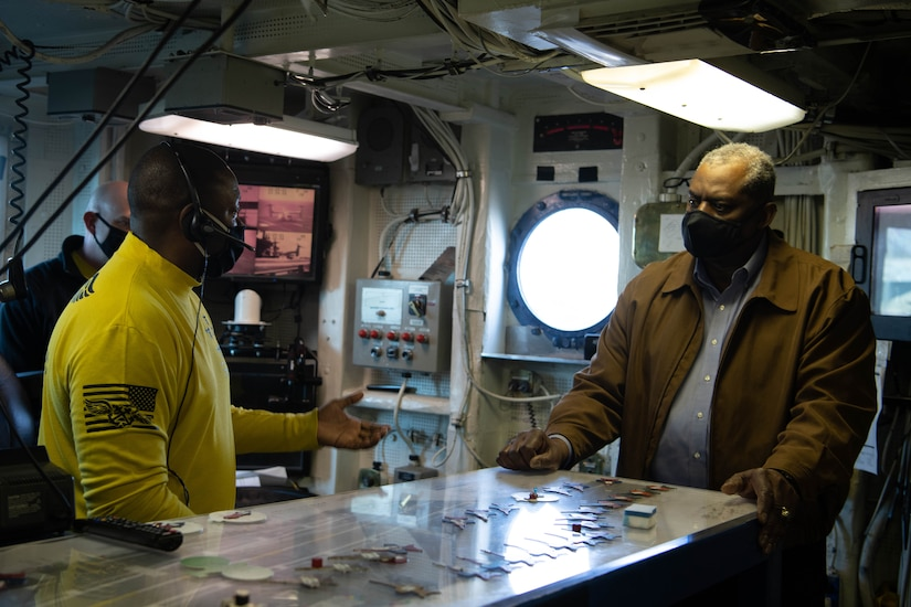 Two men wearing face masks speak in a room on a Navy ship.