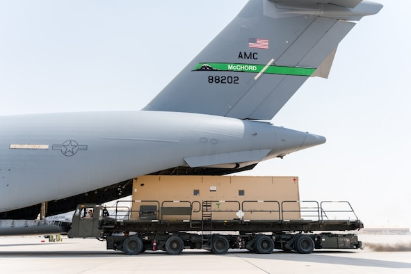 U.S. Air Force Airmen assigned to the 8th Expeditionary Air Mobility Squadron offload a Negatively Pressurized Conex-Lite from a C-17 Globemaster III at Al Udeid Air Base, Qatar, Aug. 3, 2020. The NPC-Lite is an isolated containment chamber designed to transport individuals with infectious diseases, such as COVID-19. (U.S. Air Force photo by Staff Sgt. Lauren Parsons)