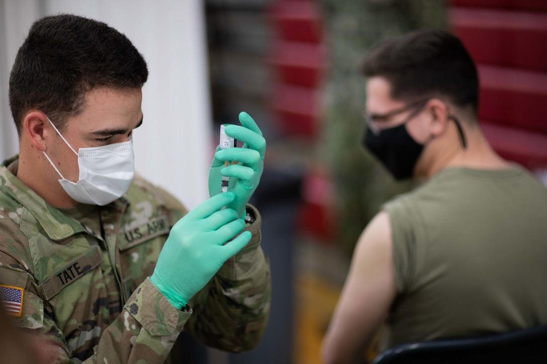 A soldier holds a syringe.
