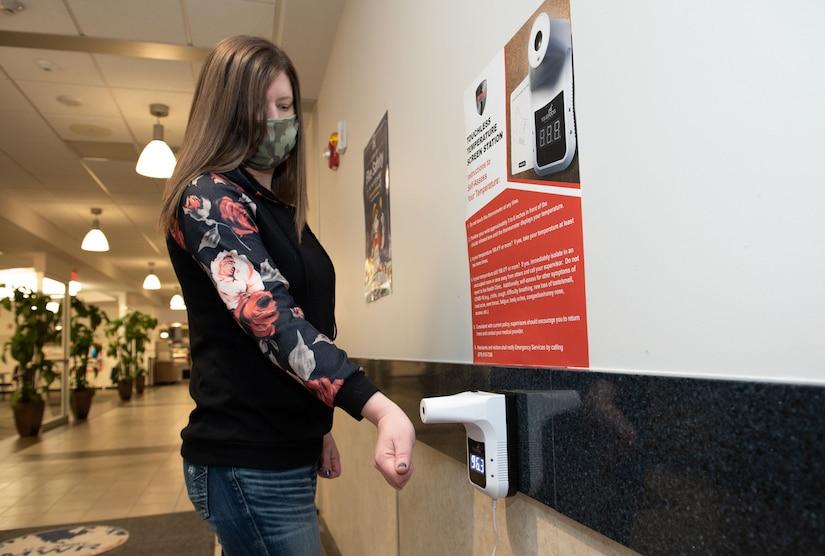 Photo of Dana Bilotta demonstrating self temperature checks.