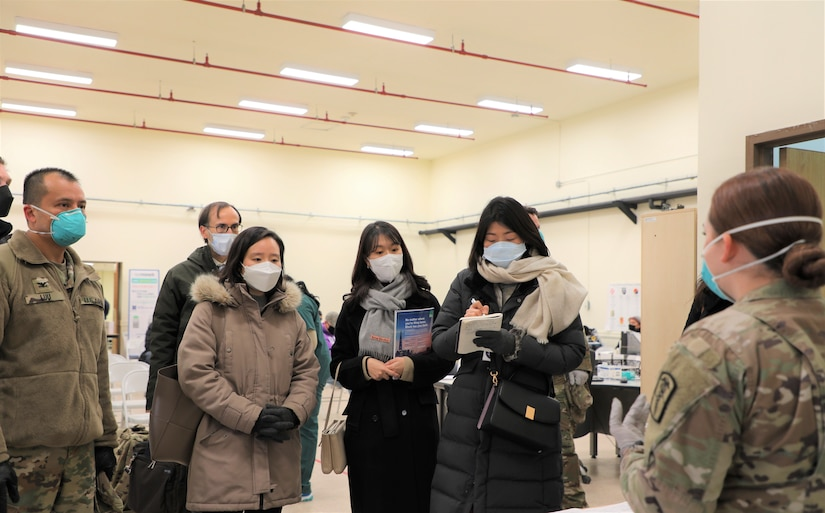 South Korean disease control workers listen to a U.S. soldier.