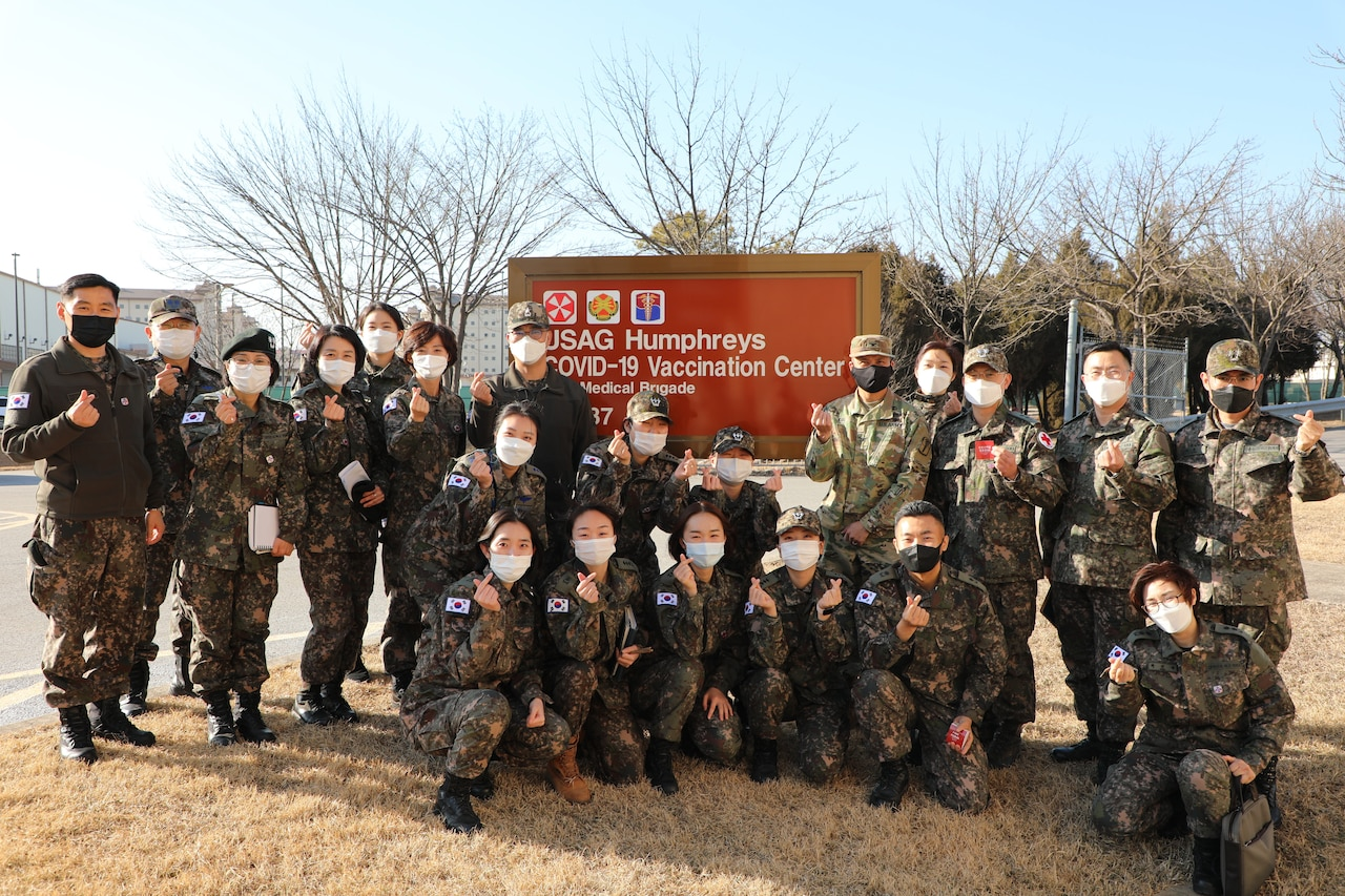 Korean and U.S. soldiers pose for a picture while making heart signs with their hands.