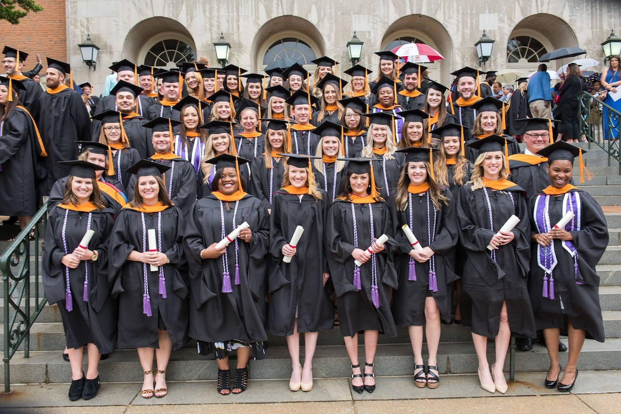A large group of people wearing graduation caps and gowns pose for a photo on steps.