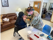 Staff Sgt. Herbert Lins, 3-238th Aviation (MEDEVAC) gives the COVID-19 vaccination to a patient at the CMC Retirement Village as part of the Targeted Vaccination Team in St. Louis, Mo. February 18, 2021