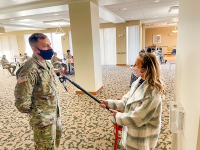Missouri Army National Guard Staff Sgt. Jeremy Brown, 1107th TASMG, being interviewed by Emma Hogg of KMOV at a targeted vaccination team site in St. Louis on February 24, 2021.