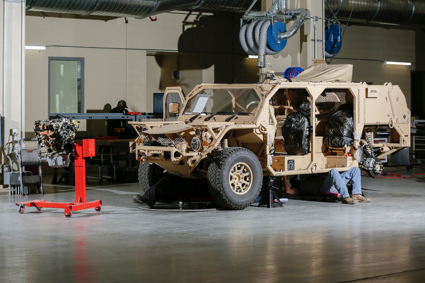 Heavy Mobile Equipment mechanics work with Flyer Defense personnel to learn every aspect of maintenance and repair of the Special Operations' Ground Mobility Vehicle at Production Plant Barstow, Marine Depot Maintenance Command, aboard the Yermo Annex of Marine Corps Logistics Base Barstow, Feb 24.