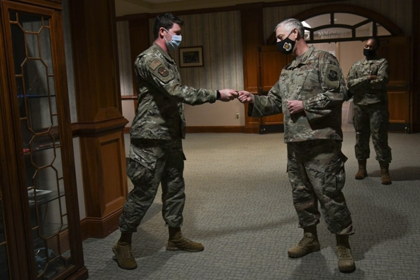 Airman 1st Class David Jenkins, from the 628th Comptroller Squadron,  gets coined by Maj. Gen. Mark Camerer, U.S. Air Force Expeditionary Center commander, at Joint Base Charleston, S.C., Feb. 9, 2021. Camerer, along with Chief Master Sgt. Anthony W. Green, USAF Expeditionary Center command chief, toured the base to get a firsthand look at Team Charleston's capabilities and accomplishments.