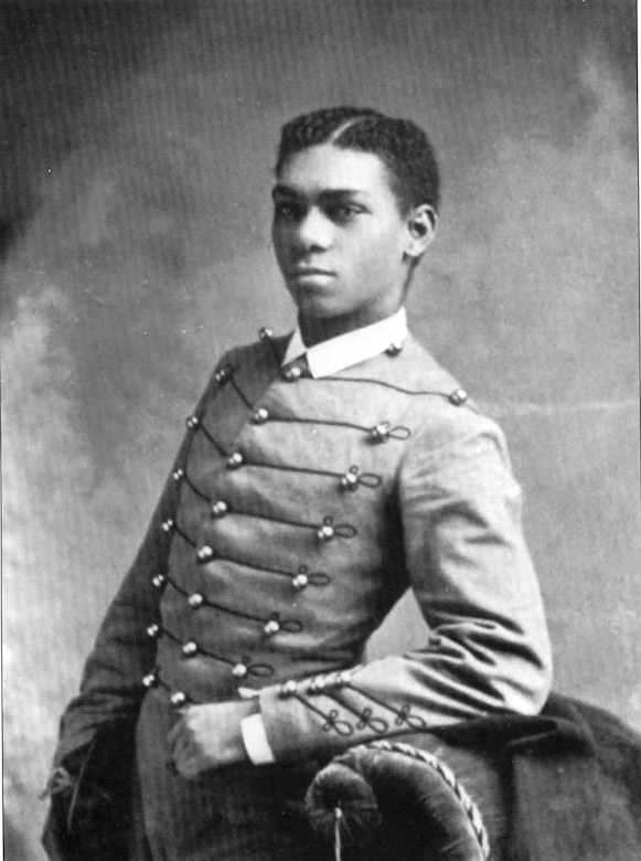 A historic photo shows a young man standing with his arm on the back of a chair.