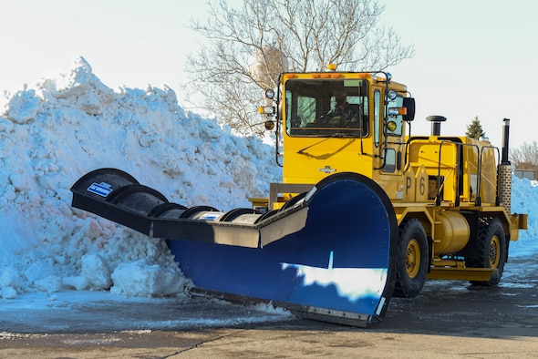 A plow with the 88th Civil Engineer Squadron snow removal team pushes snow into a snow pile on the airfield of Wright-Patterson Air Force Base, Ohio, Feb. 23, 2020. From November to April the team runs 24-hour operations with as many as 30 pieces of equipment to ensure the mission of Wright-Patt can continue.