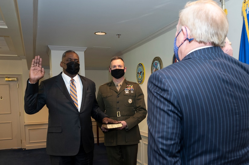 A man dressed in a business suit stands in an office with his left hand on the Bible and his right hand raised. A man wearing a military uniform holds the Bible; another man with his back to the camera is in the foreground. All three men wear face masks.