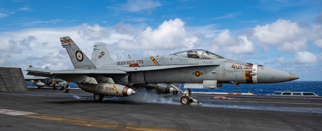 "210219-N-JX182-1148 PACIFIC OCEAN (Feb. 19, 2021) An F/A-18C Hornet, from the ""Death Rattlers"" of Marine Fighter Attack Squadron (VMFA) 323, launches off the flight deck of the USS Nimitz (CVN 68). Nimitz, flagship of Nimitz Carrier Strike Group, is currently conducting routine operations in U.S. Third Fleet. (U.S. Navy photo by Mass Communication Specialist 3rd Class Charles DeParlier/Released)"