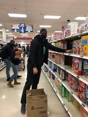 A volunteer stocks a shelf with dry cereal in the commissary on Goodfellow Air Force Base, Texas, Feb. 17, 2021. Winter Storm Uri increased the demand for nonperishable items and left shelves empty. (Courtesy photo)