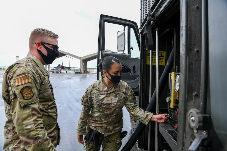 U.S. Air Force Tech Sgt. Chaz Wise, a quality assurance evaluator from the 18th Logistic Readiness Squadron, instructs Senior Airman Jamaila Centino, a member from the 18th Wing Security Forces Squadron, on refueling procedures during a Multi-Capable Airmen course exercise on Kadena Air Base, Japan, Feb. 26, 2021. The MCA course is conducted over five days, and includes three tiers of training, each more in-depth than the last.