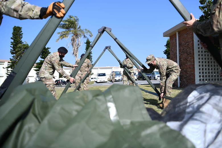 """U.S. service members from the 18th Wing practice assembling a multi-use tent during a Multi-Capable Airmen course exercise, at Kadena Air Base, Japan, Feb. 24, 2021. This training is a part of the """"beddown procedures"""" portion of the course, preparing Airmen to set up facilities in any location necessary."""
