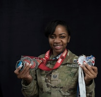 Tsgt. Shaneka hunter poses with her medals from various obstacle course races