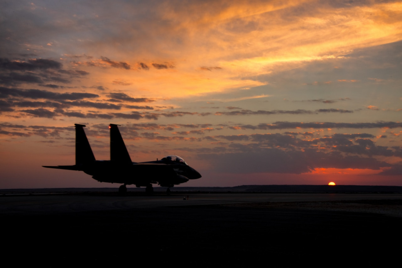 A fighter aircraft is seen on the ground against the setting sun.