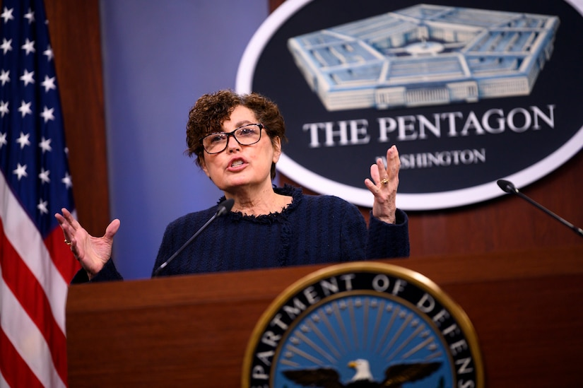 """A woman stands behind a lectern. In the rear, a sign on the wall reads """"The Pentagon - Washington."""""""