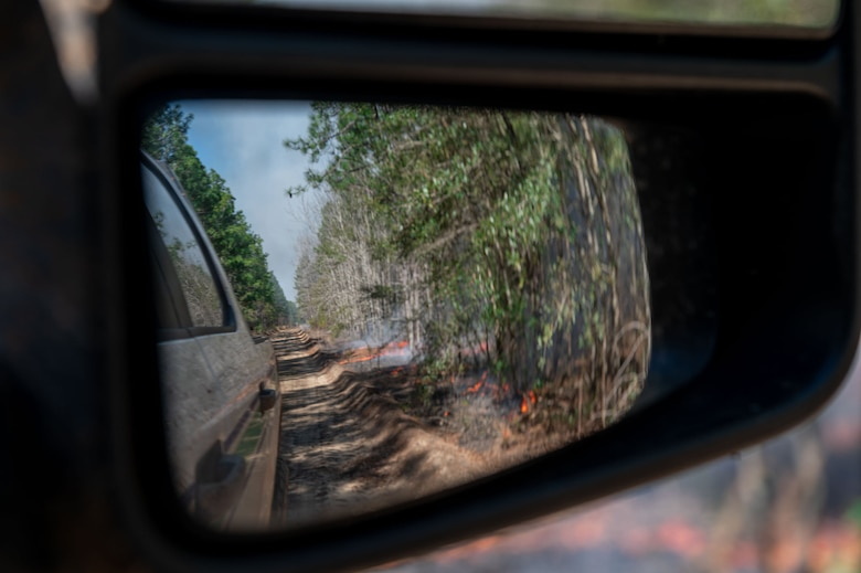 A photo of a sideview mirror with a fire reflected in it.